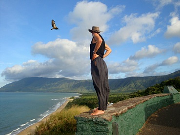 man standing on cliff watching eagle in sky
